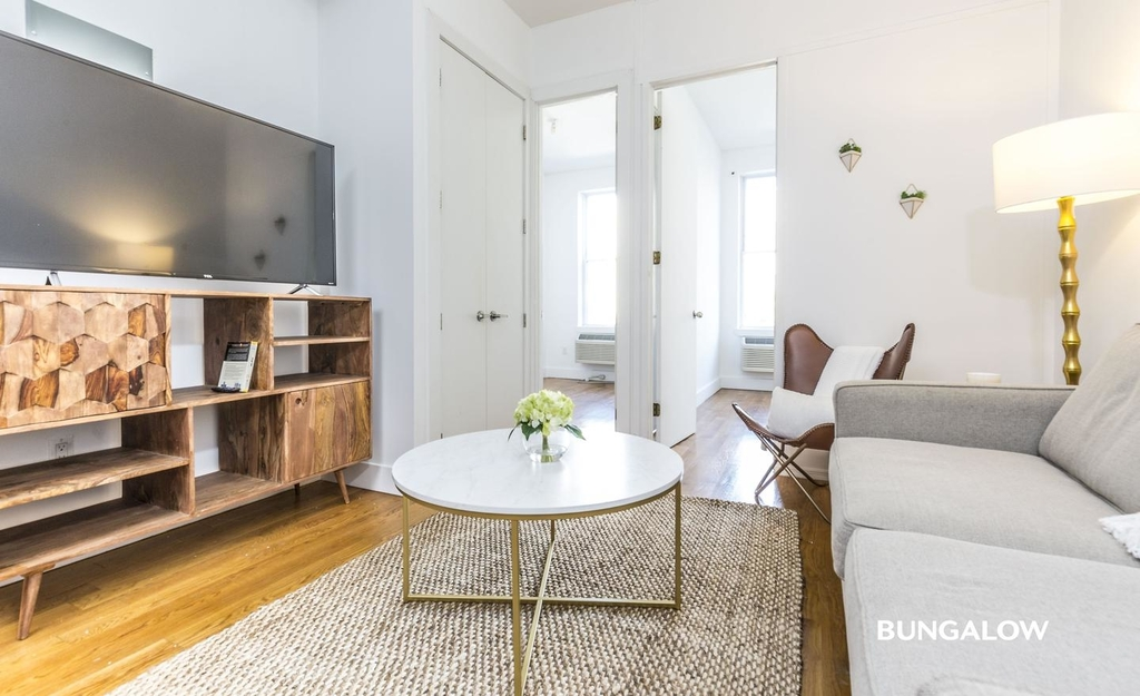 apartment listing photo of living room with tv, coffee table, and sofa